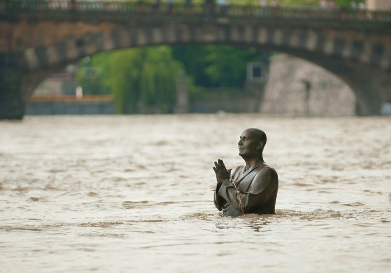 Скульптура молящегося человека под водой